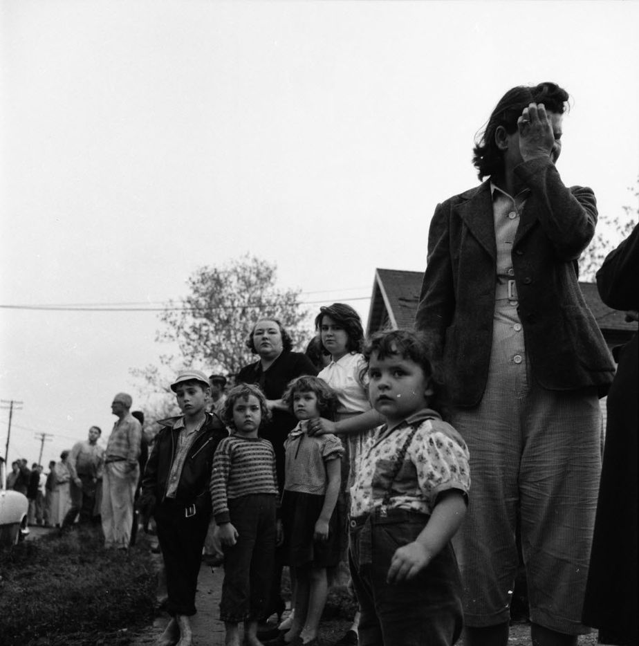 Families lined a street in Dallas to survey the damage after the 1957 tornado.