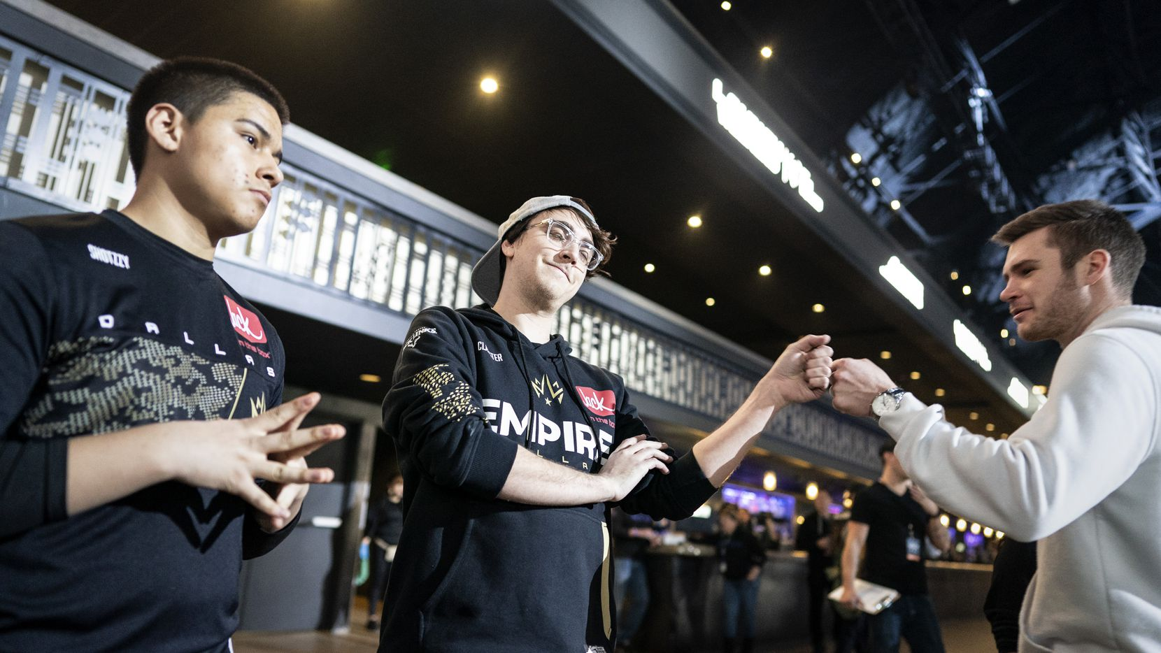 Clayster (James Eubanks), center, greets a fan as he and teammate Shotzzy (Anthony Cuevas-Castro), left, prepare for the Dallas Empire's match against the Chicago Huntsmen in the Call of Duty League Launch Weekend at the Armory in Minneapolis, Minn., January 24, 2020.