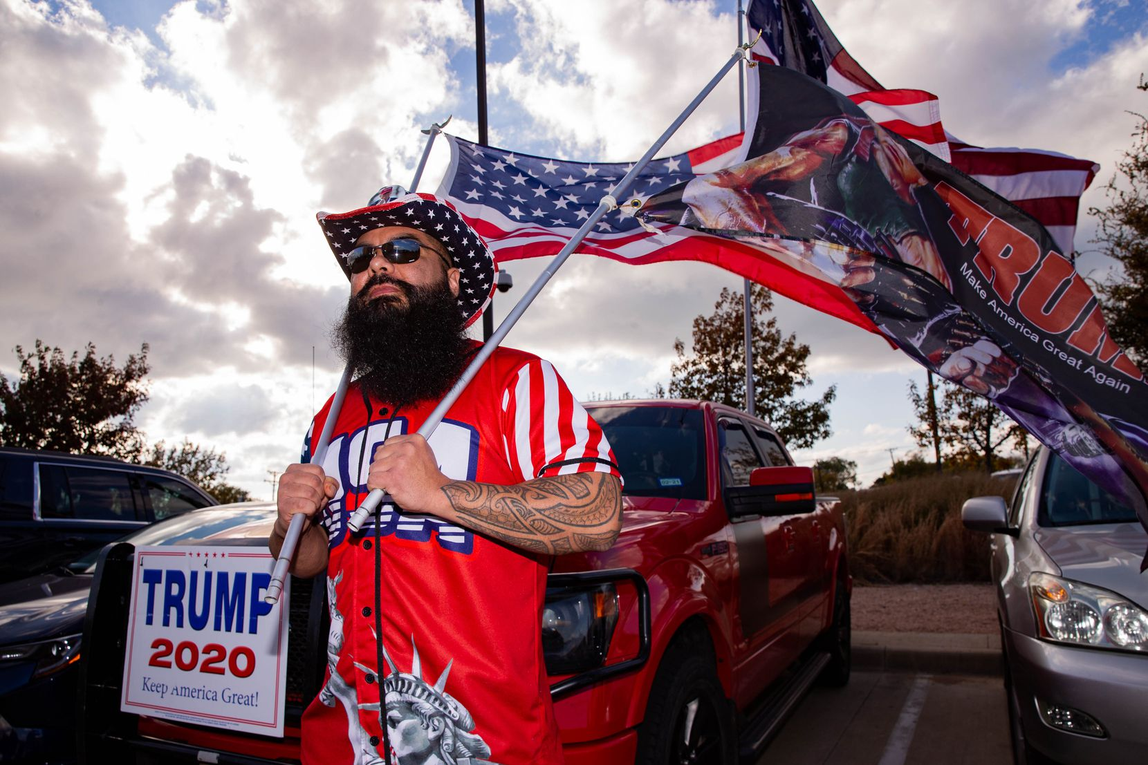 John Varela from Van Zandt County flies his flags in support of President Donald Trump during an America is Great rally hosted by TrumpTrain 2020 DFW at Rockwall County Courthouse in Rockwall on Sunday, Nov. 8, 2020.