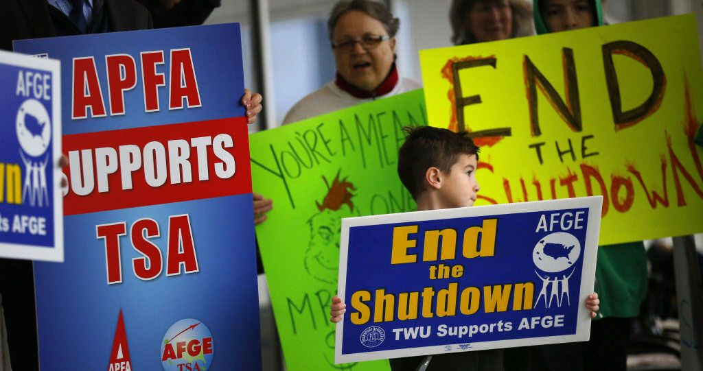 Airport employees and their families protest the government shutdown on Jan. 16 outside of Terminal D at Dallas-Fort Worth International Airport.