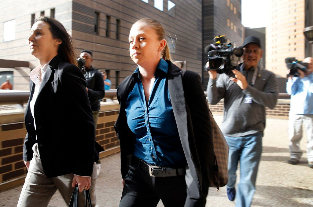 Former Dallas police Officer Amber Guyger (center) leaves the Frank Crowley Courts Building in downtown Dallas after her attorneys and a prosecutor met with the judge overseeing her case. Guyger is accused of shooting and killing Botham Jean last year in his apartment.
