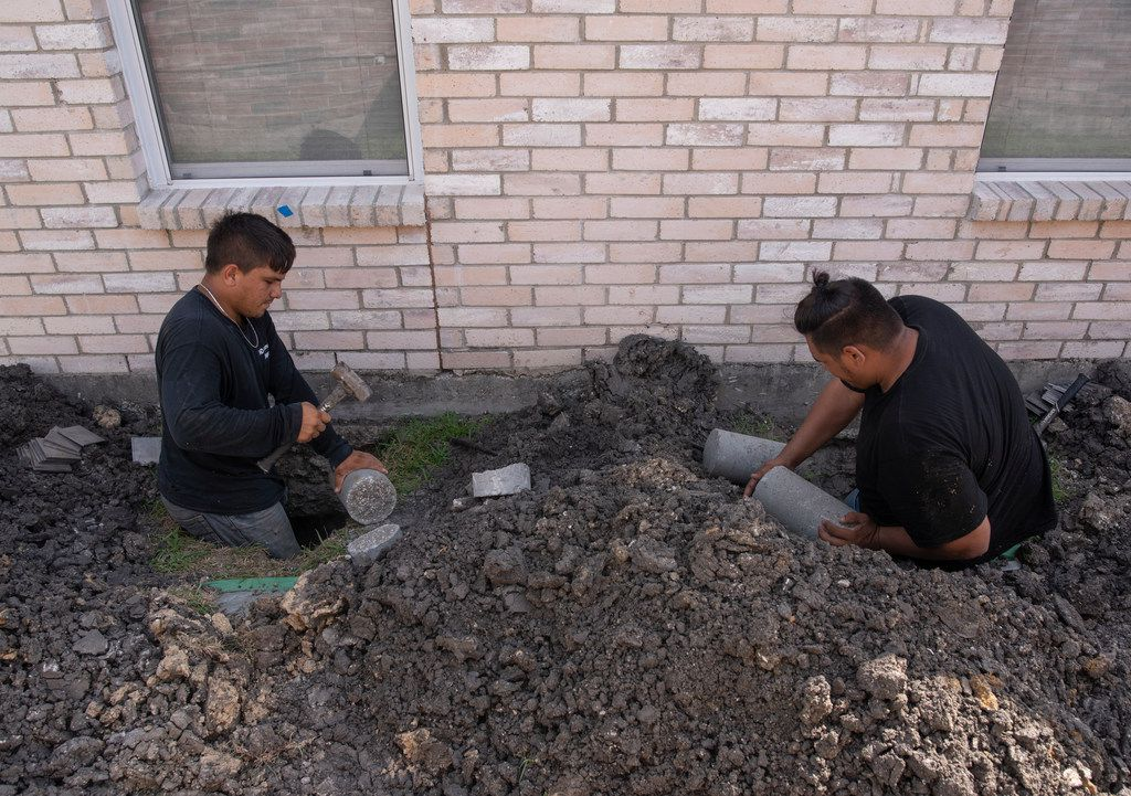 Nelson Rodriguez (left) and Asnider Rodriguez, employees with HD Foundations, put concrete pilings under a house that the company is leveling in Mesquite.