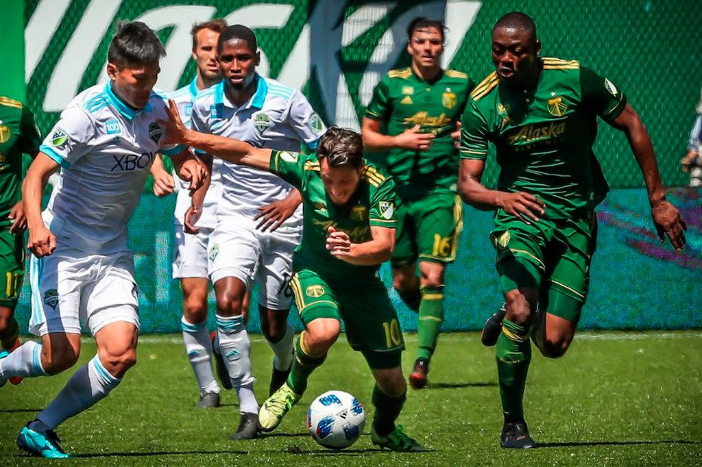 Portland Timbers midfielder Sebatian Blanco, center, tries to keep the ball against a Seattle Sounders player during an MLS soccer match in Portland, Ore., Sunday, May 13, 2018. The Timbers won, 1-0. (Serena Morones/The Oregonian via AP)