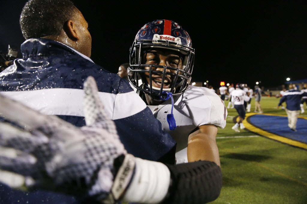 Bishop Dunne defensive back Chevin Calloway (1) celebrates with head coach Michael Johnson after winning the TAPPS football state championship game between Bishop Dunne and Prestonwood at Tiger Stadium in Corsicana, Texas Friday December 5, 2014. Bishop Dunne beat Prestonwood 41-10. (Andy Jacobsohn/The Dallas Morning News)