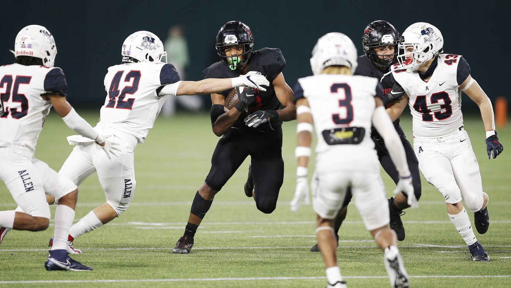Euless Trinity junior running back Ollie Gordon, center, looks for room against the Allen defense during the first half of a high school Class 6A Division I Region I semifinal football game at Globe Life Park in Arlington, Saturday, December 26, 2020.