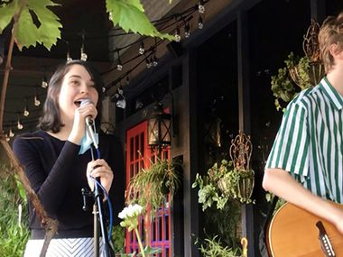 """Local singers Sam Wood and Olivia Hughes are shown performing at Sweet Firefly in the II Creeks Plaza in Richardson during an """"ice cream for breakfast"""" event in December 2020."""