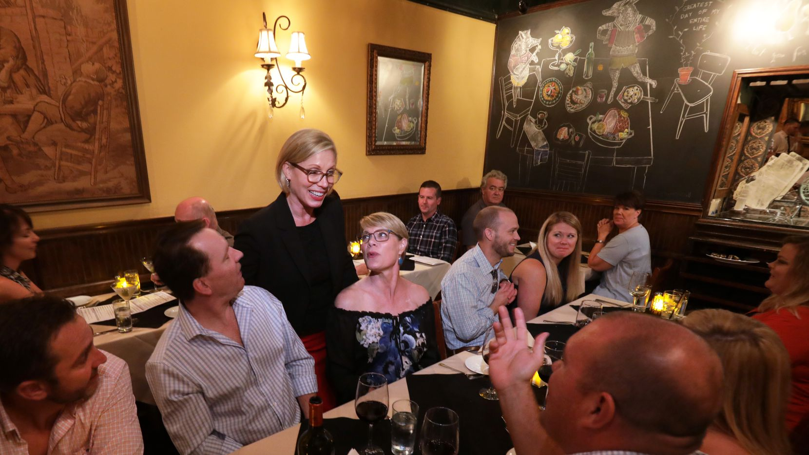 Owner Courtney Luscher checks in with diners during the busy last days of the Grape.