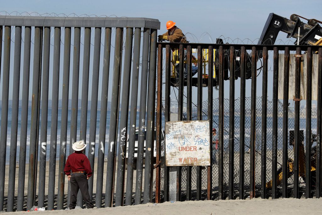 A man on the U.S. side of the border, top, works on the border structure as a man looks on, at the beach seen from Tijuana, Mexico, Thursday, Nov. 15, 2018