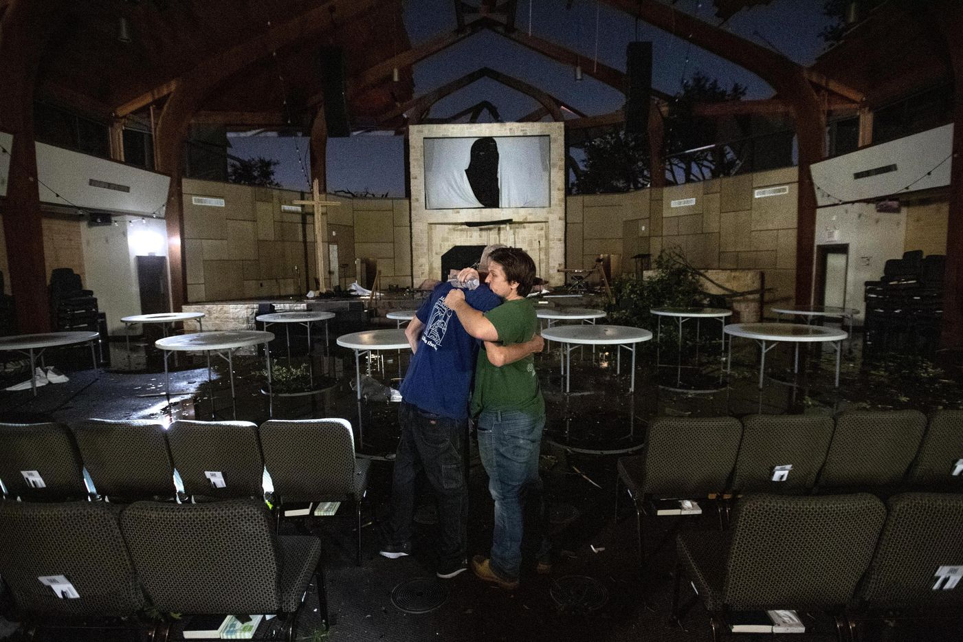 In this Sunday, Oct. 20, 2019 photo, Matt Younger, right, a pastor at Northway Church, embraces facilities associate Robert Lusk in their church's severely damaged sanctuary after a tornado tore through North Dallas.