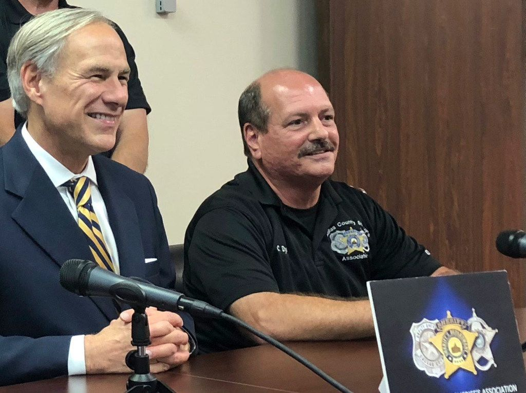 Gov. Greg Abbott, with Chris Dyer, president of the Dallas County Sheriff's Association, received the endorsement of the group for his re-election during a news conference in Dallas on Thursday.