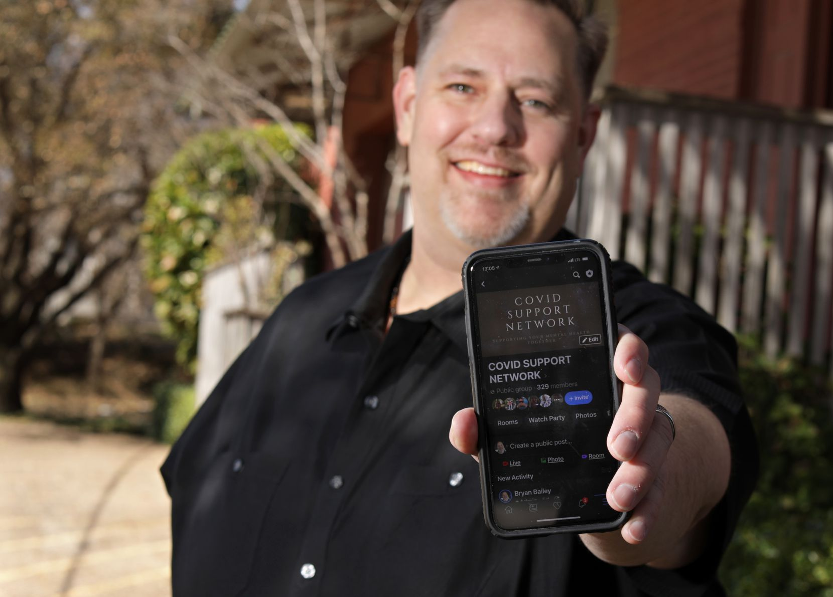 Bryan Bailey shows off his COVID support group accessed through his phone, as he poses for a photograph near his home in Dallas, TX, on Mar. 7, 2021. (Jason Janik/Special Contributor)