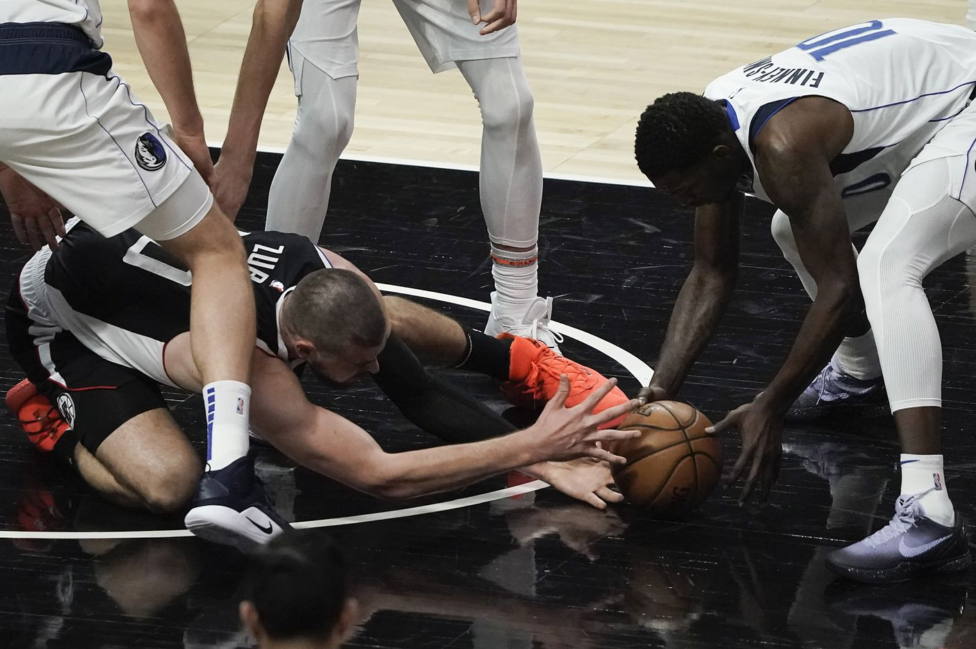 Dallas Mavericks forward Dorian Finney-Smith (10) grabs a loose ball from LA Clippers center Ivica Zubac (40) during the first half of an NBA playoff basketball game at Staples Center on Saturday, May 22, 2021, in Los Angeles.