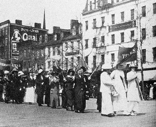 A group of Texas Women, led by three dressed in white, marched in a suffrage parade under the  Texas banner in Washington, D. C., on April 7, 1913.