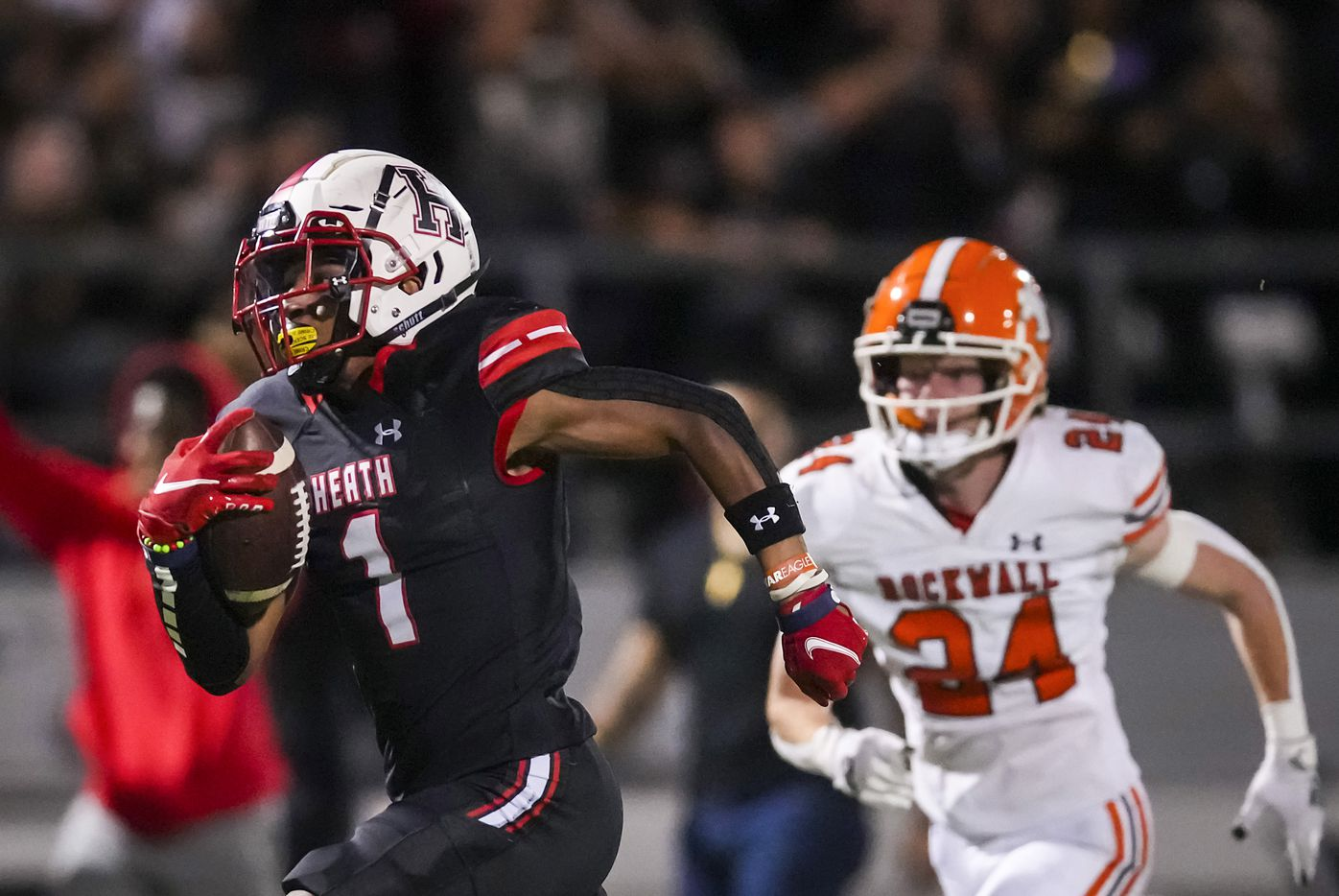 Rockwall-Heath wide receiver Jay Fair (1) races to the end zone on a 69-yard touchdown reception as Rockwall defensive back Will Rakow (24) defends during the first half of a District 10-6A high school football game at Wilkerson-Sanders Stadium on Friday, Sept. 24, 2021, in Rockwall.