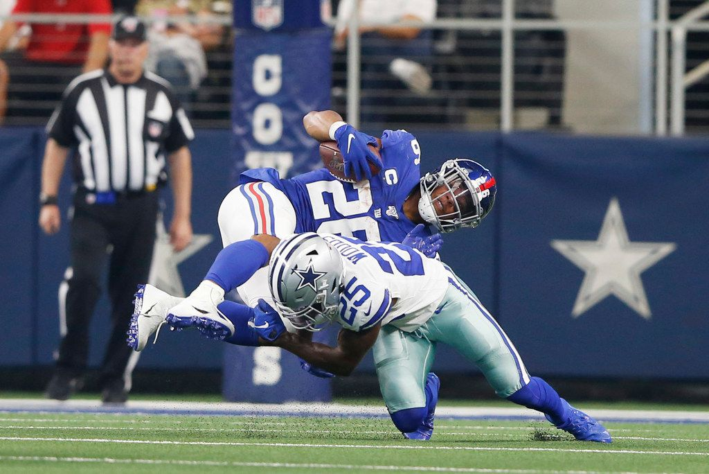 Dallas Cowboys free safety Xavier Woods (25) tackles New York Giants running back Saquon Barkley (26) during the second half of play at AT&T Stadium in Arlington, Texas on Sunday, September 8, 2019. Dallas Cowboys defeated the New York Giants 35-17 in the home opener.