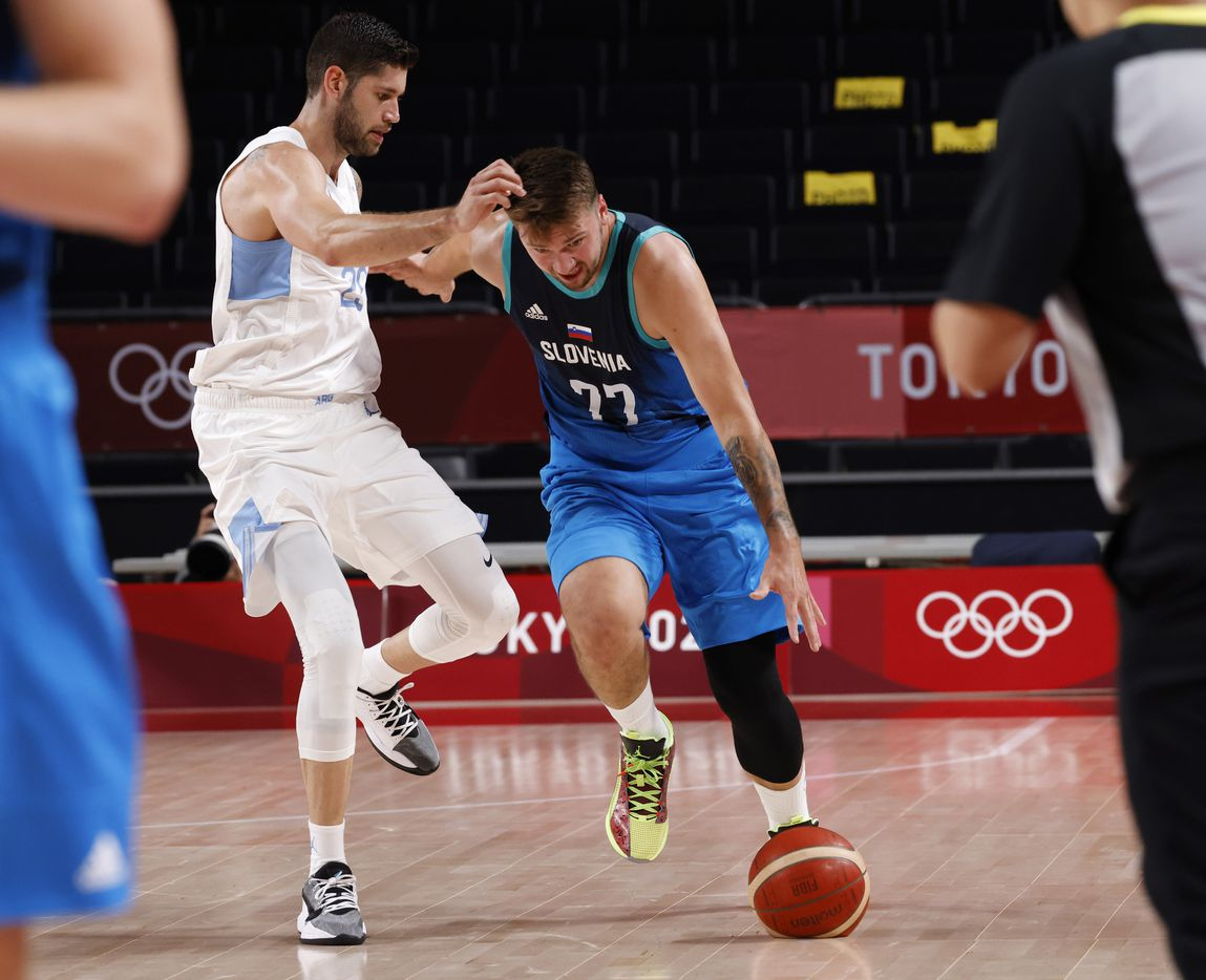 Slovenia's Luka Doncic (77) dribbles down the court as he is guarded by Argentina's Patricio Garino (29) during the postponed 2020 Tokyo Olympics at Saitama Super Arena on Monday, July 26, 2021, in Saitama, Japan. Slovenia defeated Argentina 118-100. (Vernon Bryant/The Dallas Morning News)