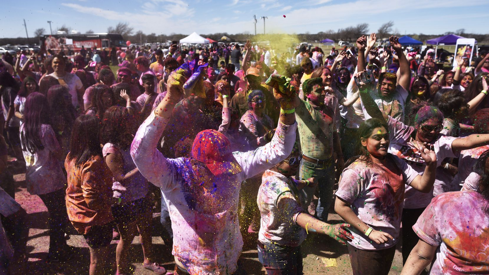 Festival goers dance and toss colored pigments during the celebration of Holi at the Dallas Festival of Colors at the Southfork Ranch.