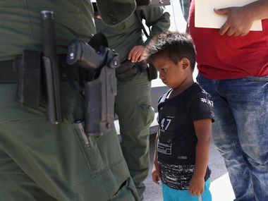 "A boy and father from Honduras are taken into custody by U.S. Border Patrol agents near the U.S.-Mexico Border on June 12, 2018 near Mission, Texas in response to the Trump administration's ""zero tolerance"" policy. (Photo by John Moore/Getty Images)"