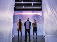 "Writer-director Ruben Carrazana (center) composer-musician Nigel Newton (left) and choreographer-dancer Emily Bernet (right) pose for a portrait inside ""The Cube"" at the Latino Cultural Center. Conceived by Carrazana and set designer Jeffery Bryant Moffitt, the sold-out production is that rare beast amid the pandemic: live theater for an in-person audience."