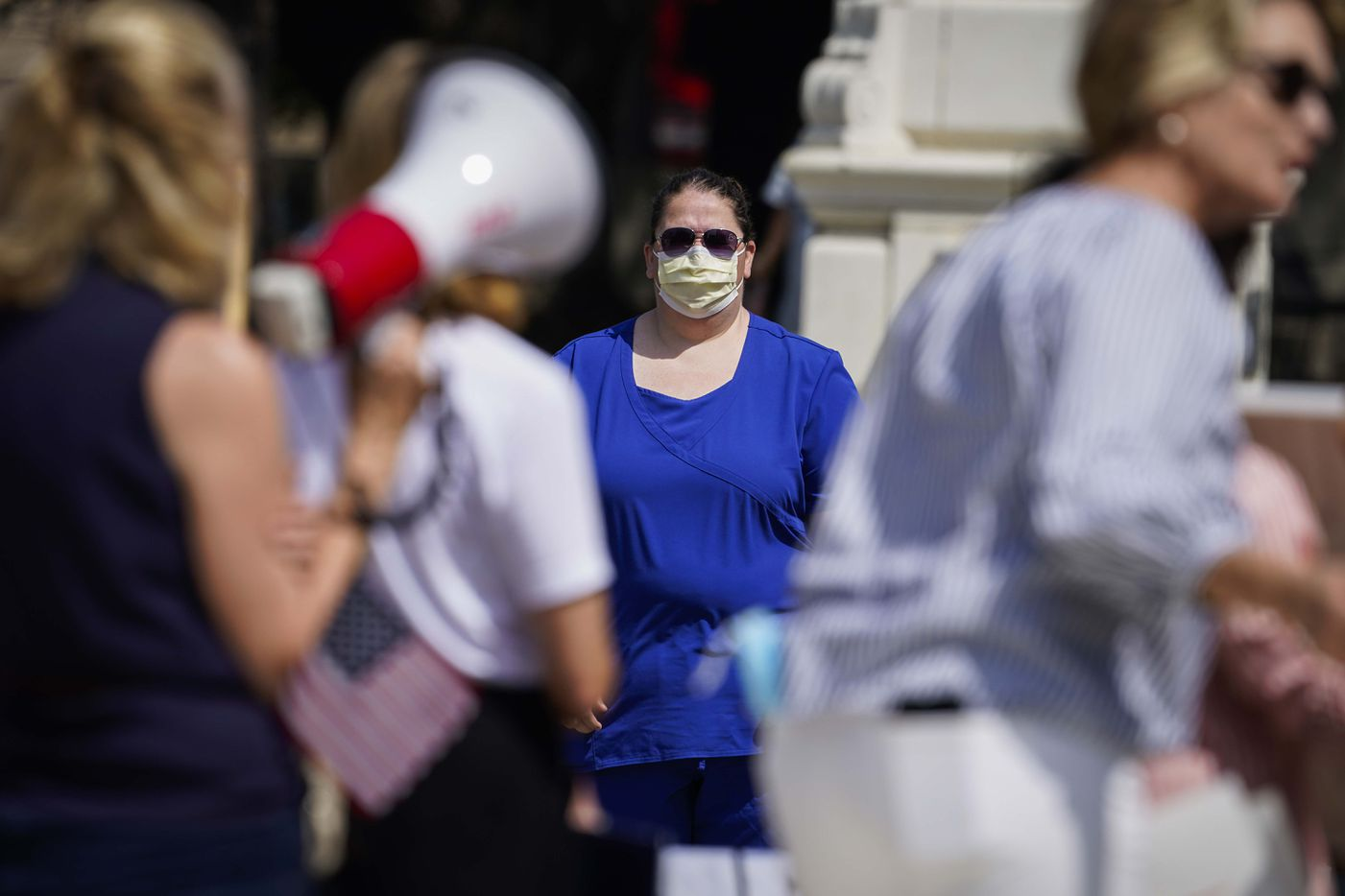 A medical worker who came to show support for social distancing measures stands across the street as protesters rally against government stay-at-home orders at Dealey Plaza on Tuesday, April 21, 2020, in Dallas.