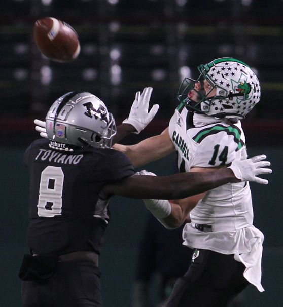 Southlake Carroll receiver Brady Boyd (14) eyes a long pass in as Arlington Martin defensive back Javien Toviano (8) moves in during first half action. The two teams played their Class 6A Division l Region l semifinal football playoff game held at Globe Life Park in Arlington on December 24, 2020. (Steve Hamm/ Special Contributor)