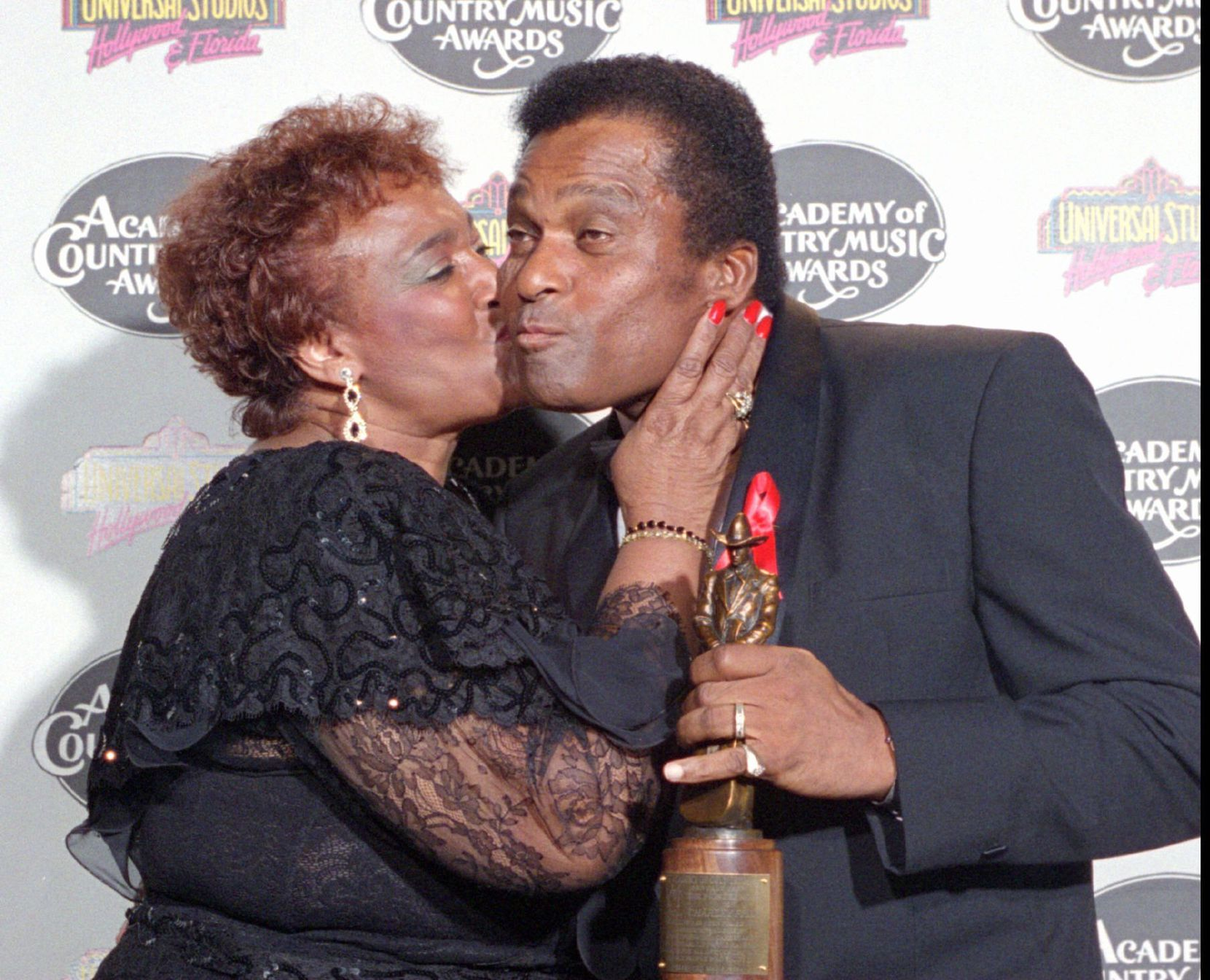 Charley Pride in 1994 getting a kiss from his wife, Rozene, after winning the Pioneer Award at the 29th Academy of Country Music Awards.