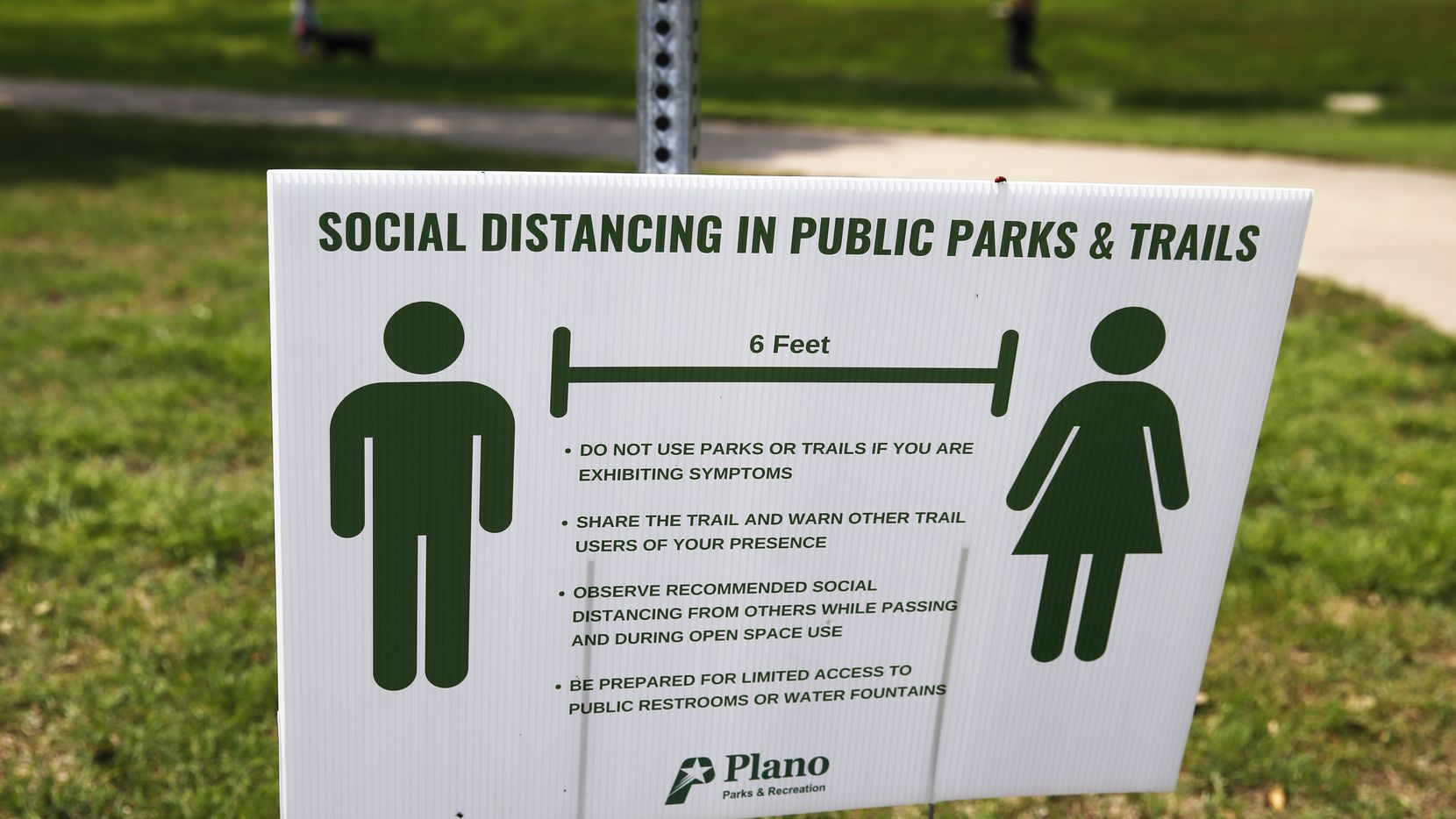 """A sign displays social distancing practices at Bob Woodruff Park in Plano, Texas on Tuesday, April 7, 2020. Plano has transferred workers from other departments to their parks to help enforce social distancing. These """"friendly monitors"""" remind people visiting the park to keep their distance.  (Vernon Bryant/The Dallas Morning News)"""