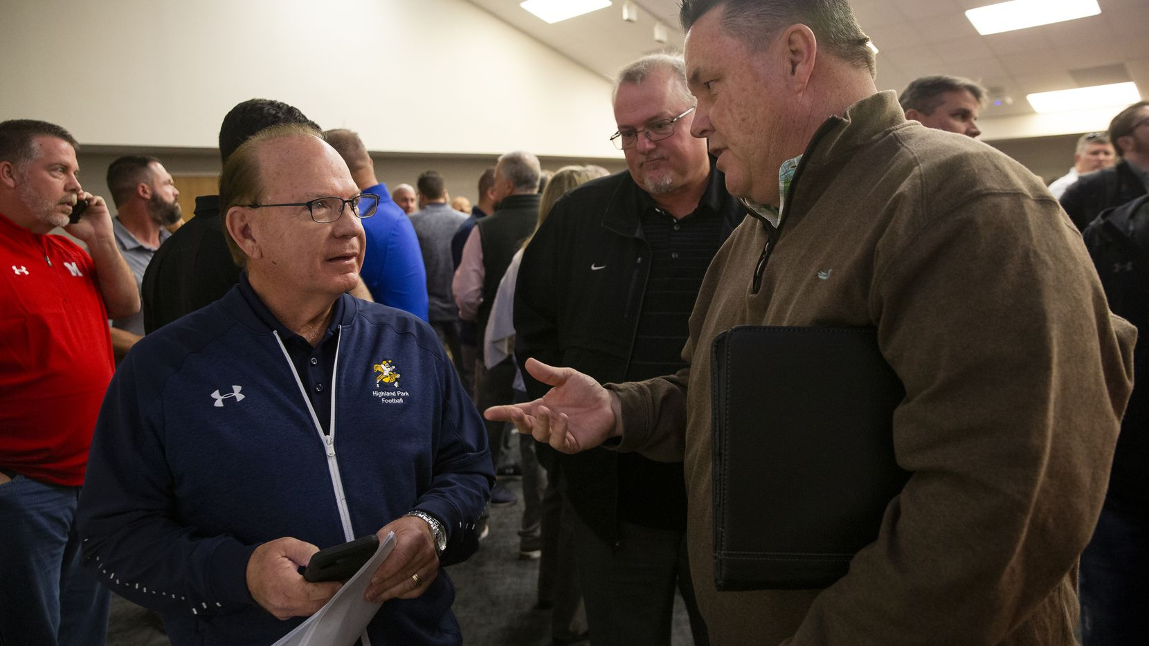 Highland Park football coach Randy Allen (left) and Rodney Webb, now the coach at Denton Guyer, chat after the UIL realignment announcement at the Birdville Fine Arts/Athletics Complex on Feb. 3, 2020.