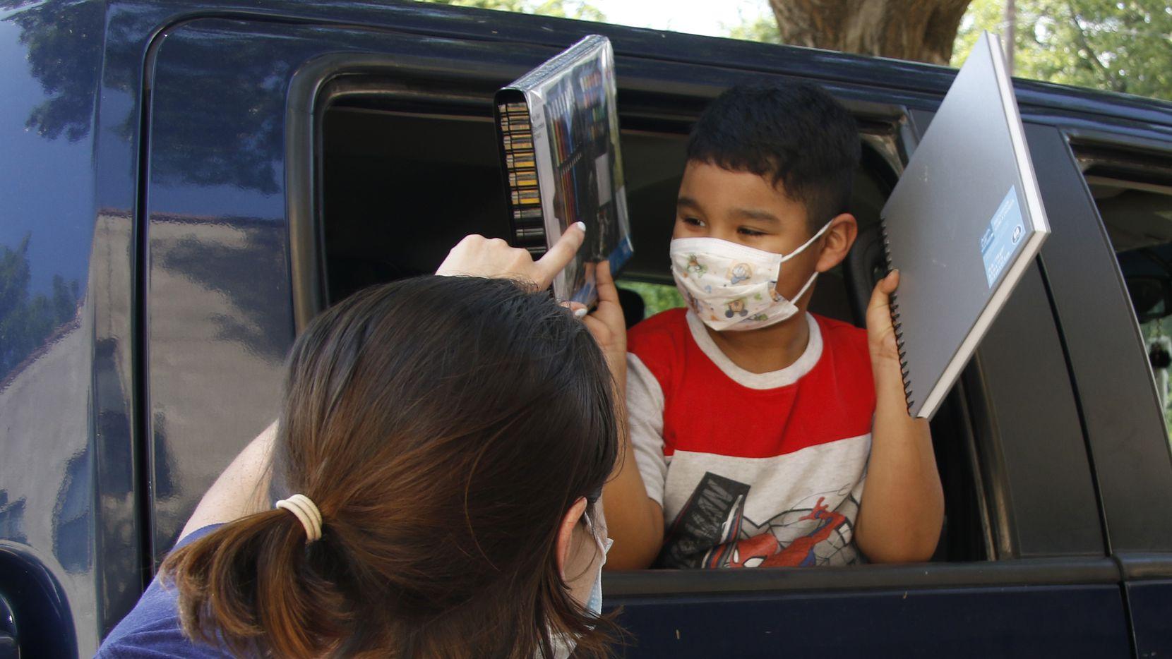 Diego Rincón, de 7 años, recibe feliz sus materiales de arte de su maestra Anden Suárez. Art House Dallas donó los materiales para los niños que participan en programas de verano en el Wesley-Rankin Community Center, en West Dallas.