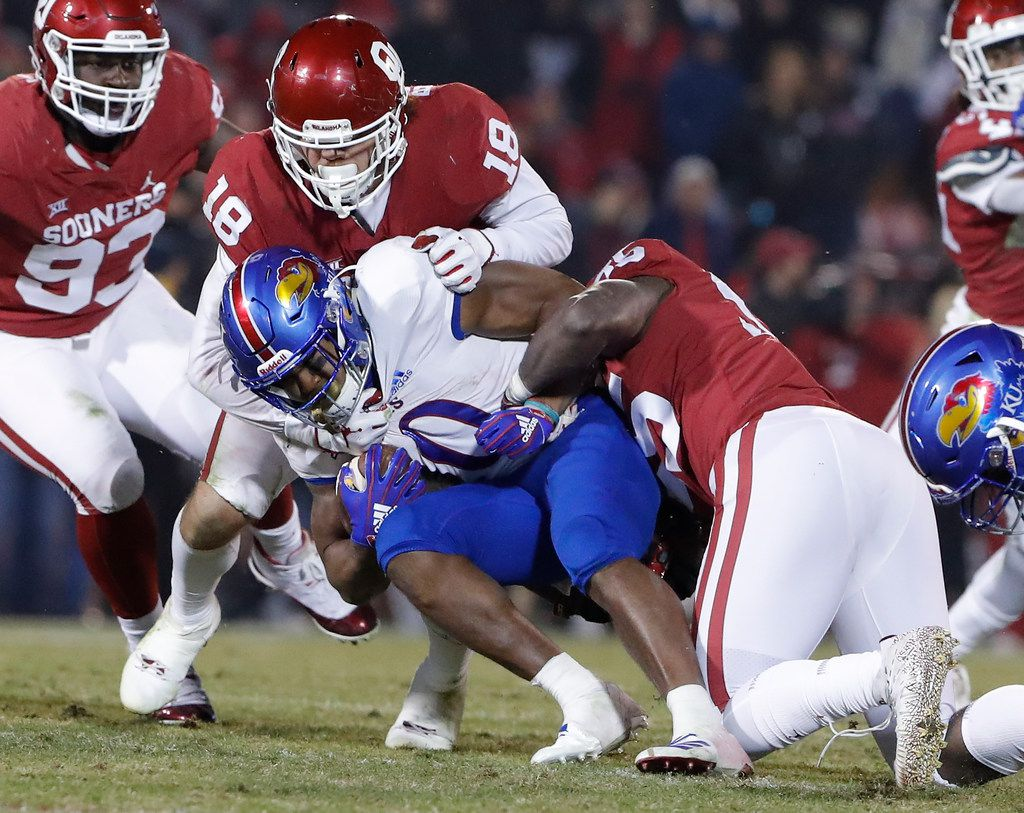 Kansas running back Khalil Herbert, center, is tackled by Oklahoma defensive lineman Kenneth Mann, right, and Oklahoma linebacker Curtis Bolton, left, during the second half of an NCAA college football game in Norman, Okla., Saturday, Nov. 17, 2018. Oklahoma won 55-40. (AP Photo/Alonzo Adams)