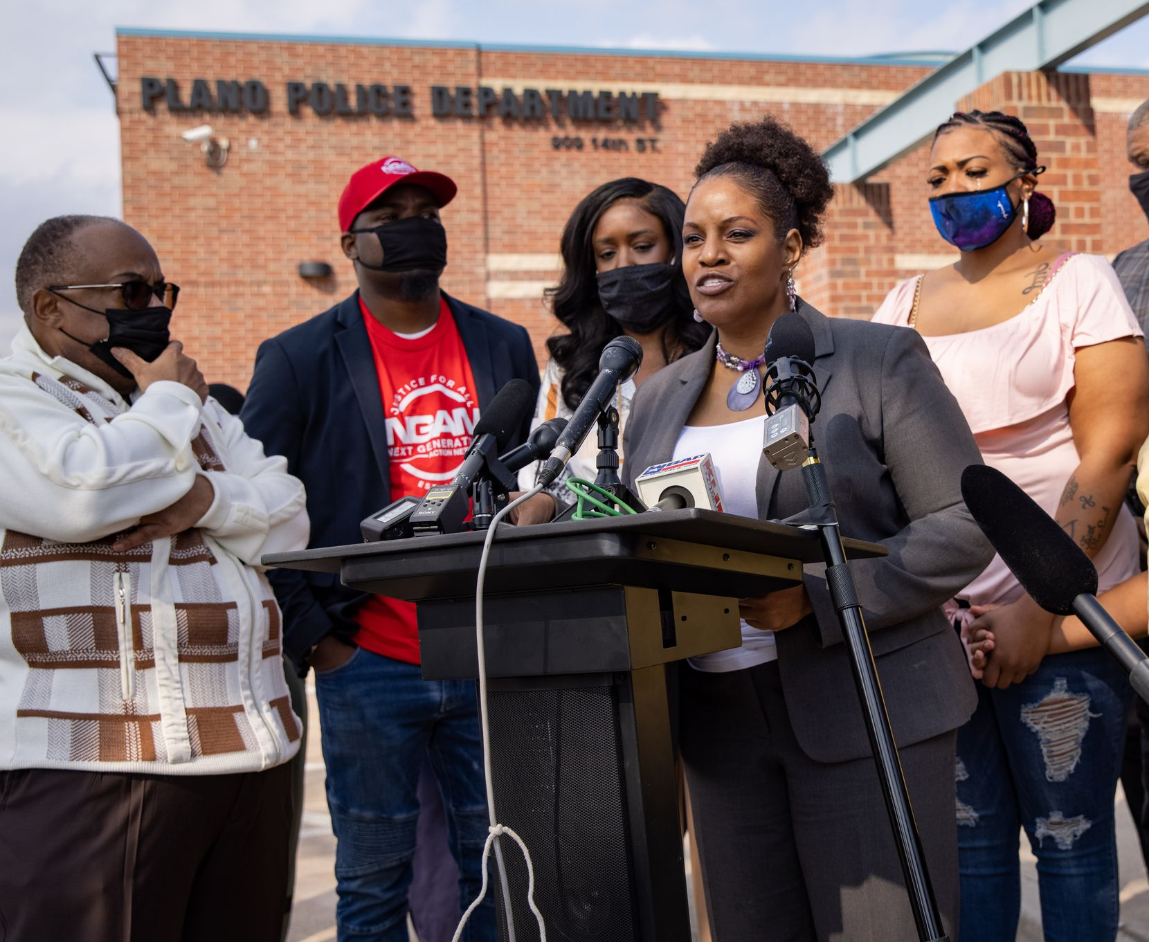 Summer Smith (right) cried as she held the hand of her son while listening to attorney Kim Cole speak during a news conference outside the Plano Police Department about the racist bullying and abuse Smith's 13-year-old son faced in March.