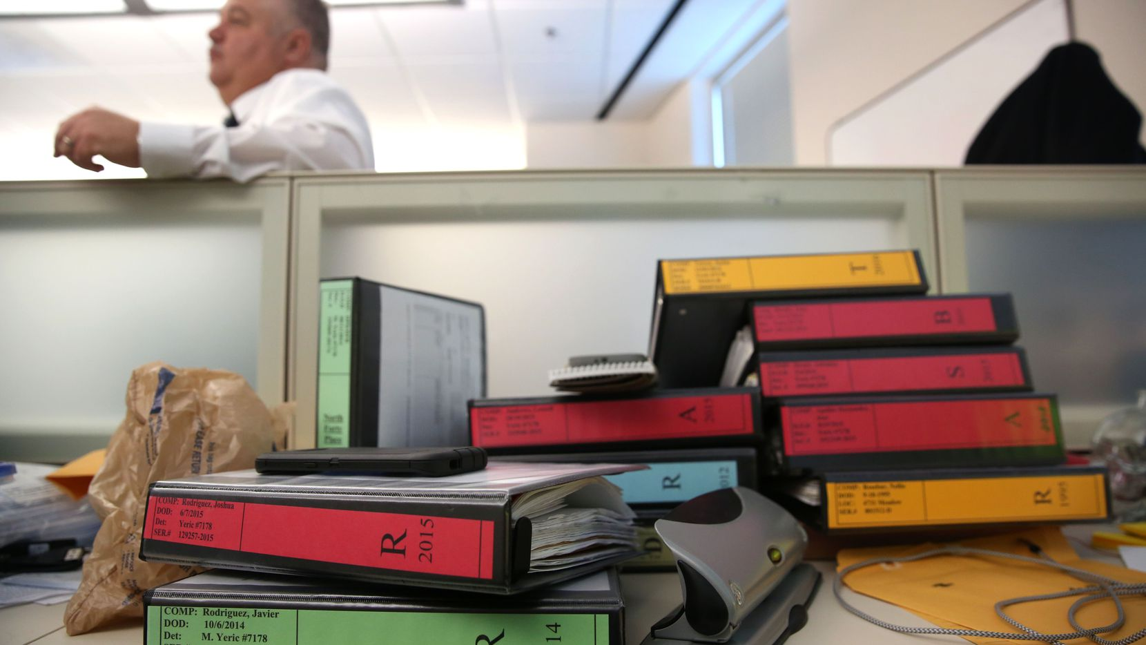 Cold case files are stacked on the desk of Det. Michael Yeric at Dallas Police Department headquarters in Dallas on Thursday, Jan. 5, 2016. (Rose Baca/The Dallas Morning News)
