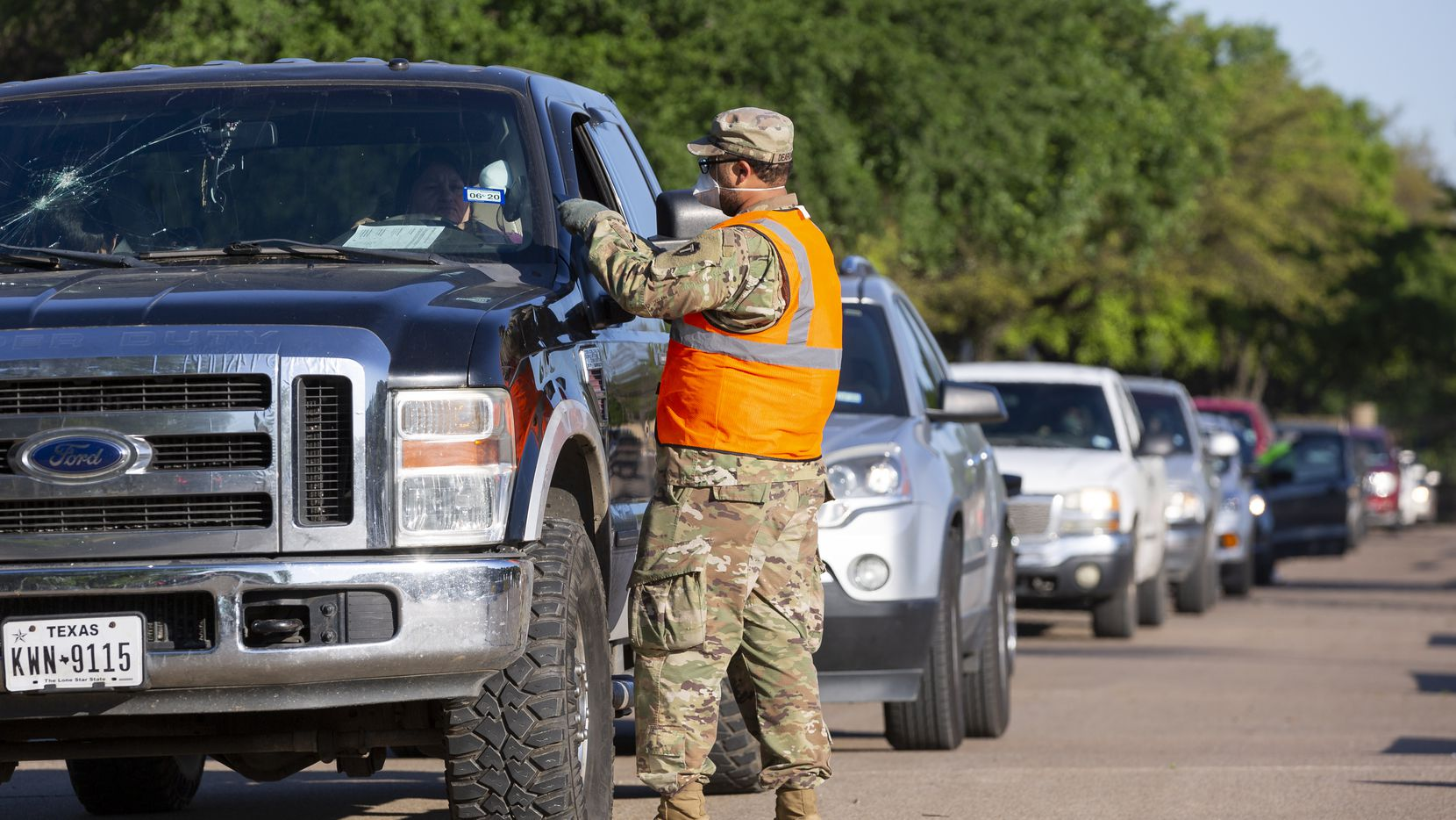A member of the Texas National Guard picks up driver's information to receive food from the North Texas Food Bank at Fair Park on Thursday.