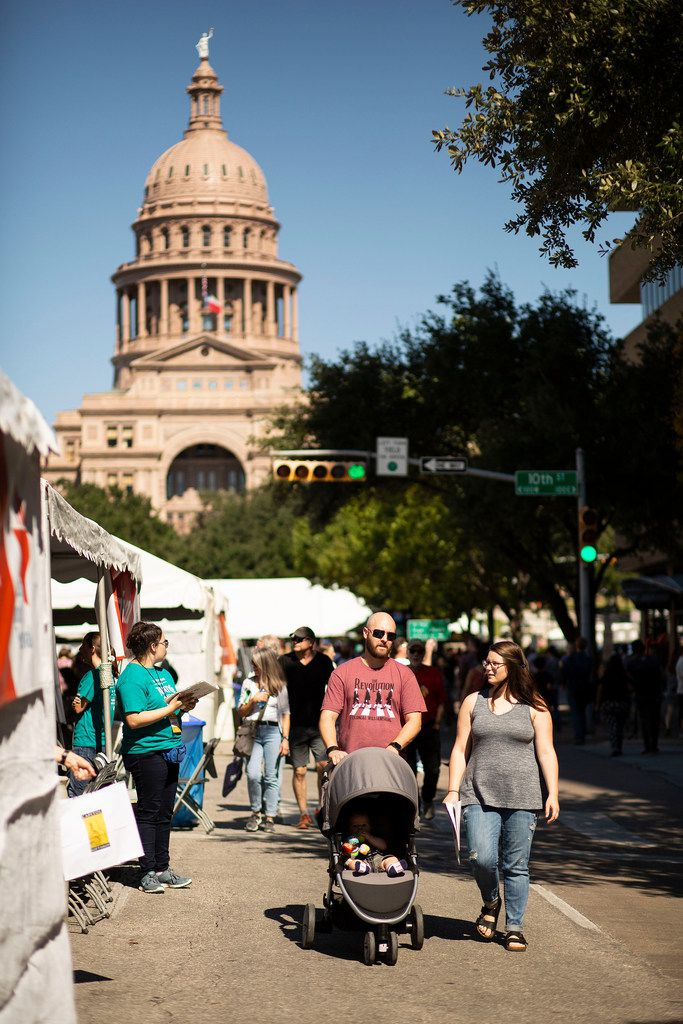 Aaron Niner and his wife Mallaree Niner walk down Congress Avenue with their son, Liam Niner, at the Texas Book Festival on Oct. 27, 2018 in Austin.
