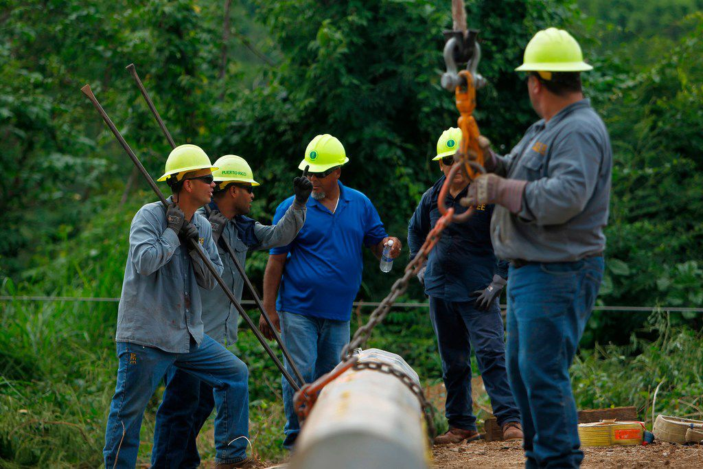 A Puerto Rico Electric and Power Authority brigade work in a remote off-road location to repair a downed power transmission line in Ponce, Puerto Rico on November 29, 2017.