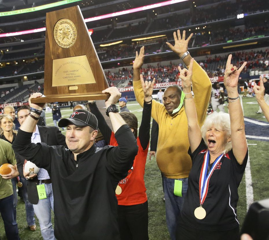 Cedar Hill head coach Joey McGuire hoists the UIL trophy after their 34-24 win for the state title during the Cedar Hill High School Longhorns vs. the Katy High School Tigers Class 5A Division II state title game at AT&T Stadium in Arlington on Saturday, December 21, 2013.