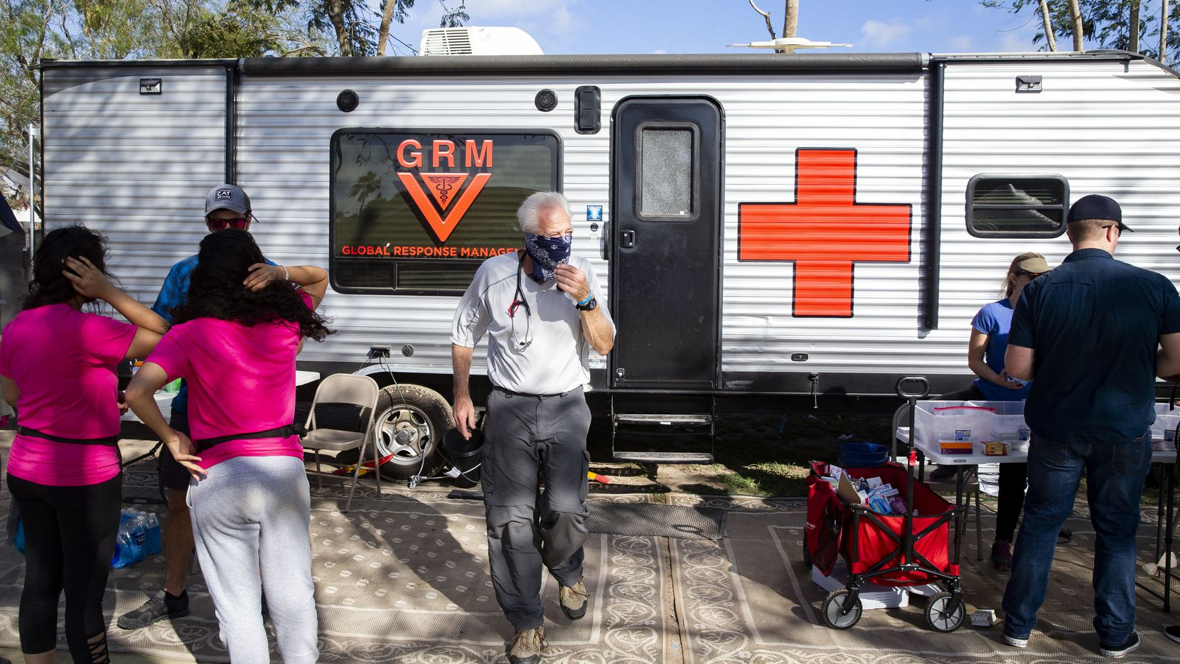 Volunteer doctors and other medical professionals set up outside the Global Response Management trailer to provide health services at the temporary camp in Matamoros, Mexico, on Sunday, Dec. 15, 2019.