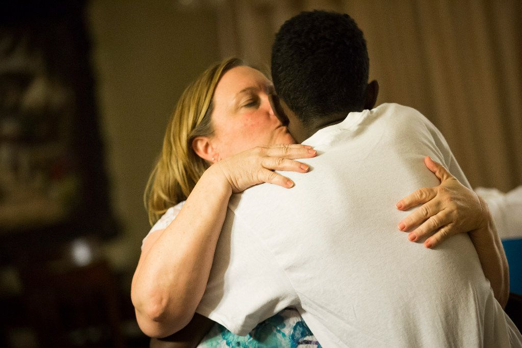 Marcos Bogale gets a kiss from his host Cheryl Zapata during a going away party for Marcos and his twin brother Tamirat on Monday, April 24, 2017, in Plano.