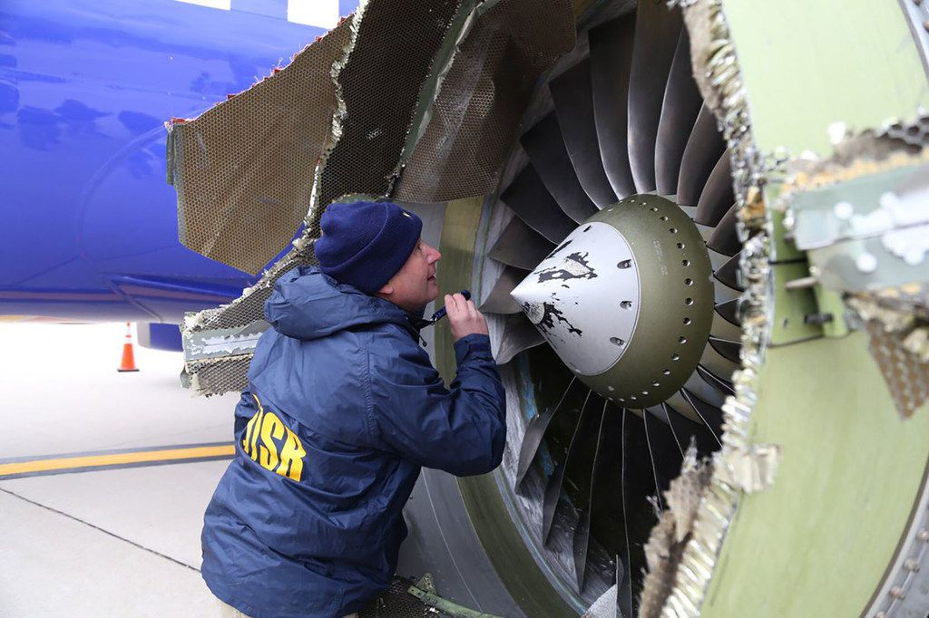 This photo obtained April 18, 2018 courtesy of the National Transportation Safety Board shows an NTSB investigator on scene examining damage to the engine of the Southwest Airlines plane on April 17, 2018. (handout)