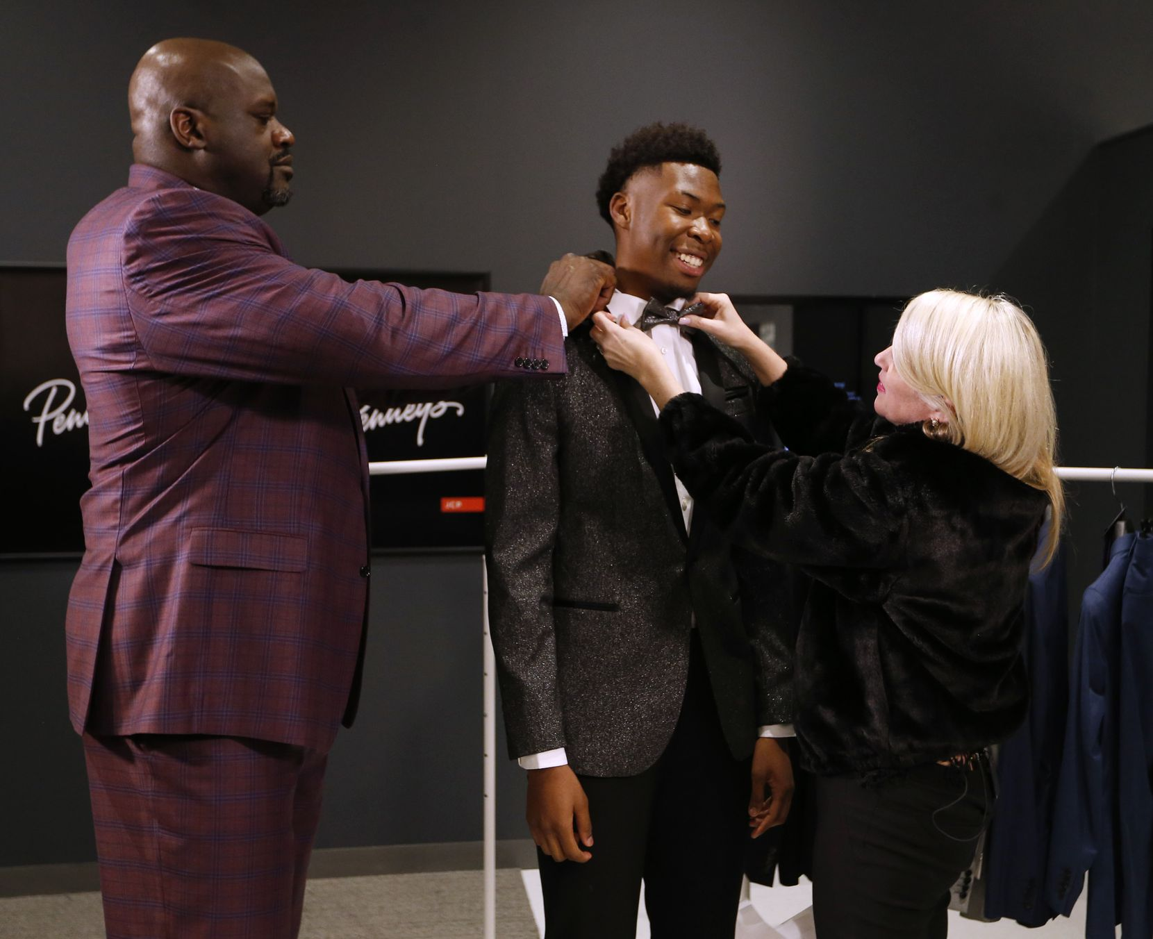 Shaquille O'Neal (left) and Sage McEuin (right), senior styling director at J.C. Penney, work on putting a tie on South Oak Cliff's Kylon Owens (center), 17, at J.C. Penney's Northeast Mall location in Hurst, Texas on Wednesday, January 15, 2020. J.C. Penney and Shaquille O'Neal surprised Owens with a big & tall wardrobe fitting at the store.