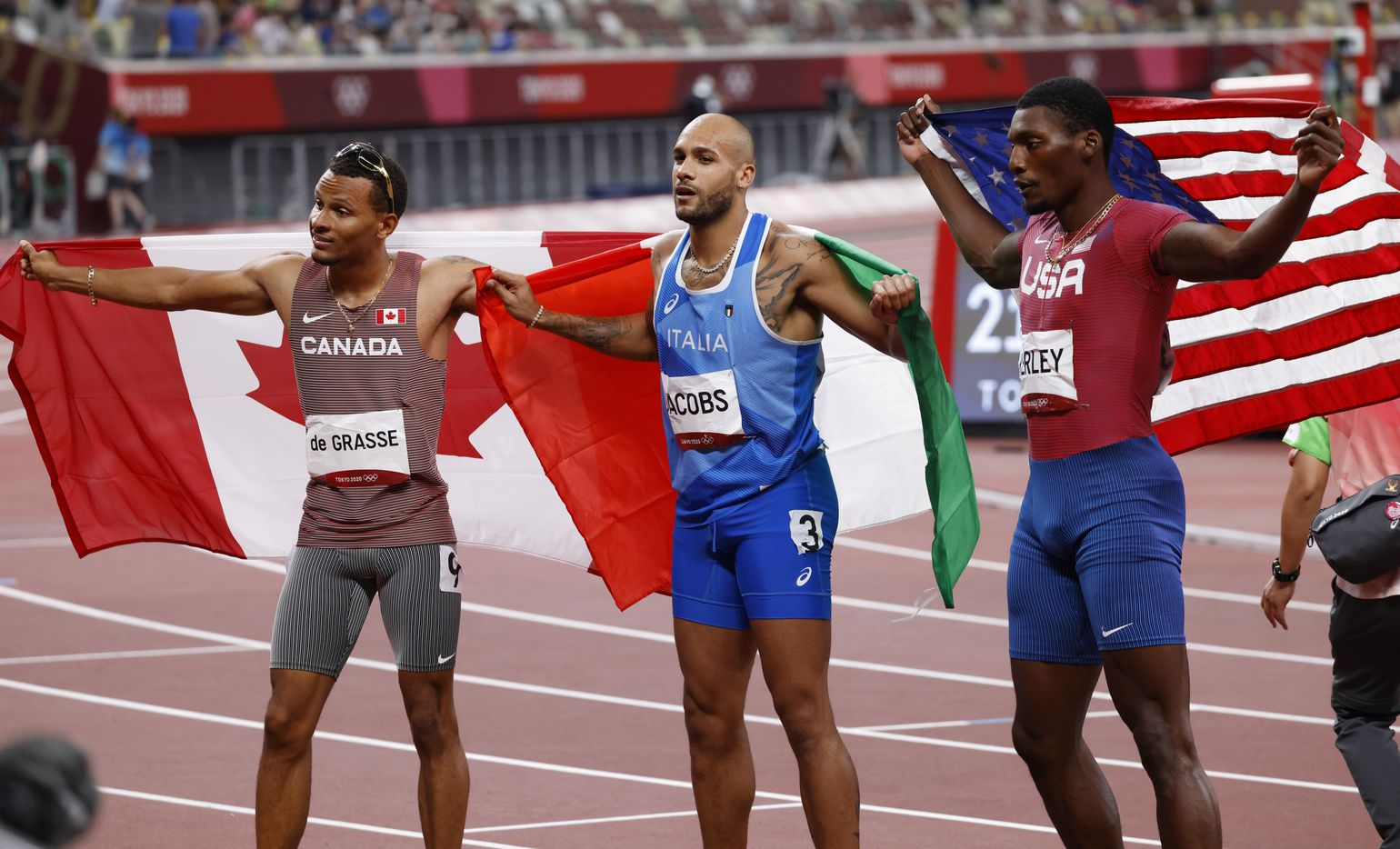 (From left to right) Canada's Andre de Grasse, Italy's Lamont Marcell Jacobs, and USA's Fred Kersey pose for photographers after competing in the men's 100 meter final   during the postponed 2020 Tokyo Olympics at Olympic Stadium, on Sunday, August 1, 2021, in Tokyo, Japan. Jacobs took first for gold, Kerly second for silver and de Grasse took third for bronze.