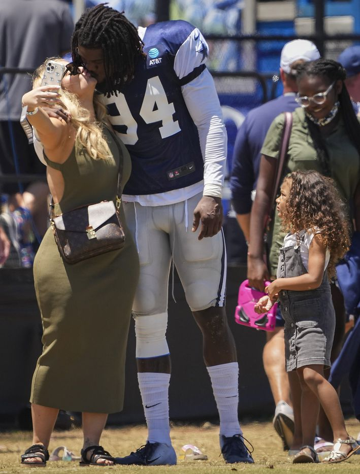 Dallas Cowboys defensive end Randy Gregory  kisses his girlfriend Nancy as they take a selfie on the field after a practice at training camp on Sunday, Aug. 1, 2021, in Oxnard, Calif.