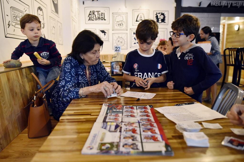 Carmen de Paoli organiza las estampas junto con otros niños en el restaurante Arepa TX, en Dallas. Niños y adultos se reúnen en el local para intercambiar estampas mundialistas para coleccionar el álbum Panini.  BEN TORRES/Especial para DMN