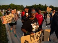 Kamona Nelson marches with other demonstrators from the Collin County Courthouse to the Collin County jail in McKinney on Tuesday after a grand jury did not indict the eight jailers involved in Marvin Scott III's death.