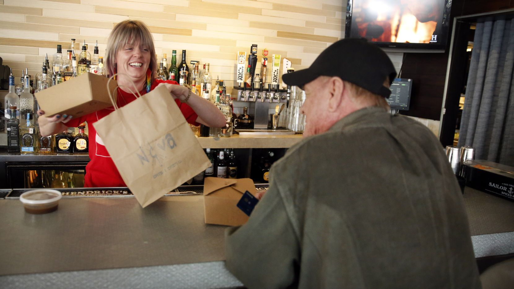 Bartender Jody Aderhold (left) packages up regular Jim Harper's food order at Nova, a popular Oak Cliff neighborhood restaurant and bar that's had to close for sit-down service because of the coronavirus, Saturday, March 21, 2020. (Tom Fox/The Dallas Morning News)