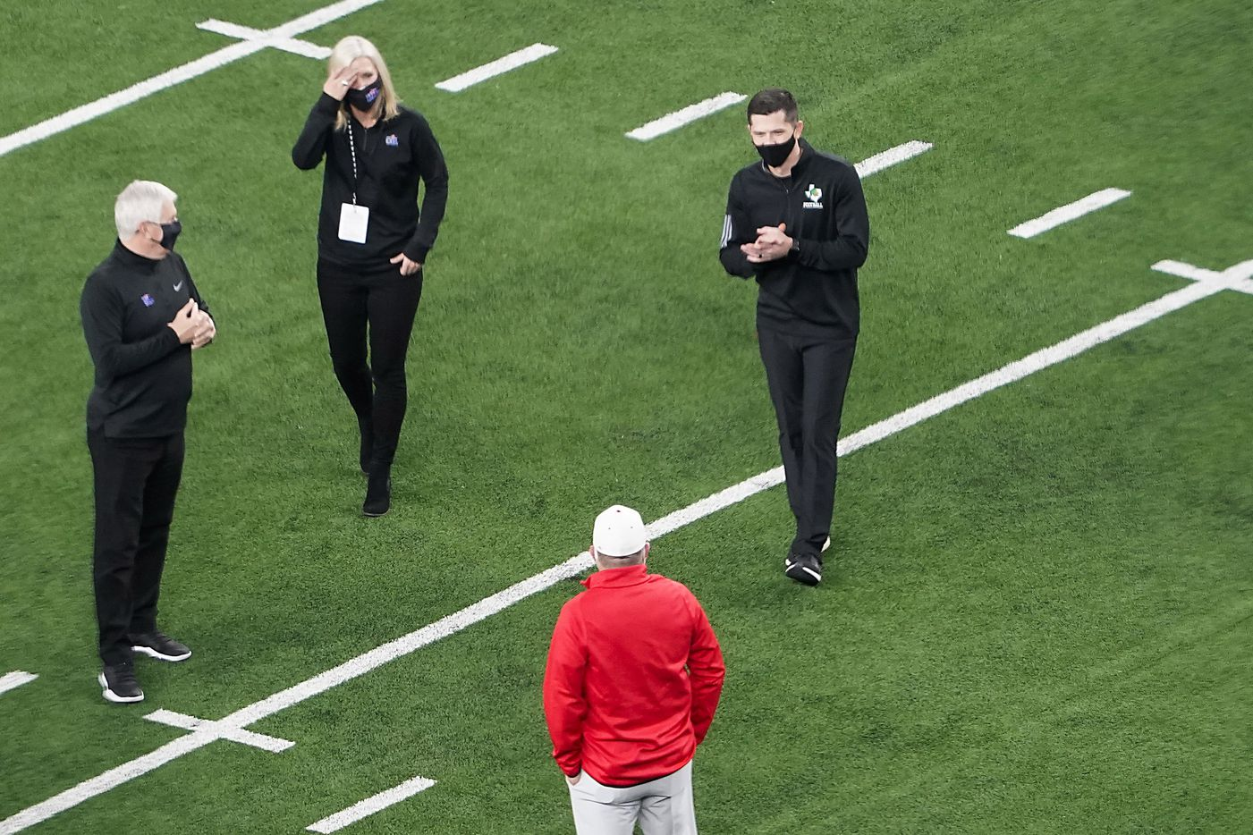 Southlake Carroll head coach Riley Dodge (top right) meets with his father, Austin Westlake head coach Todd Dodge (bottom) on the field before the two teams play for the Class 6A Division I state football championship at AT&T Stadium on Saturday, Jan. 16, 2021, in Arlington, Texas.