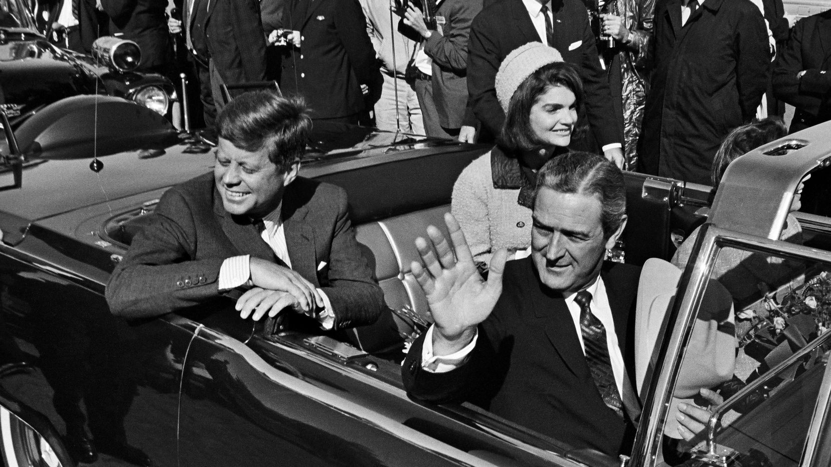 Pres. John F. Kennedy, Jacqueline Kennedy, and Texas Gov. John Connally wave as their motorcade departs Love Field to head to downtown Dallas on Nov. 22, 1963.