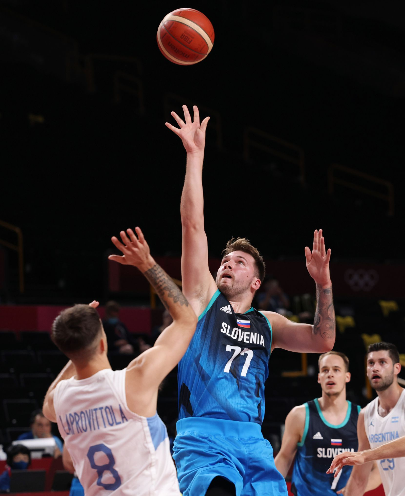 Slovenia's Luka Doncic (77) attempts a shot in front of Argentina's Nicolas Laprovittola (8) in the first half of play during the postponed 2020 Tokyo Olympics at Saitama Super Arena on Monday, July 26, 2021, in Saitama, Japan. Slovenia defeated Argentina 118-100. (Vernon Bryant/The Dallas Morning News)