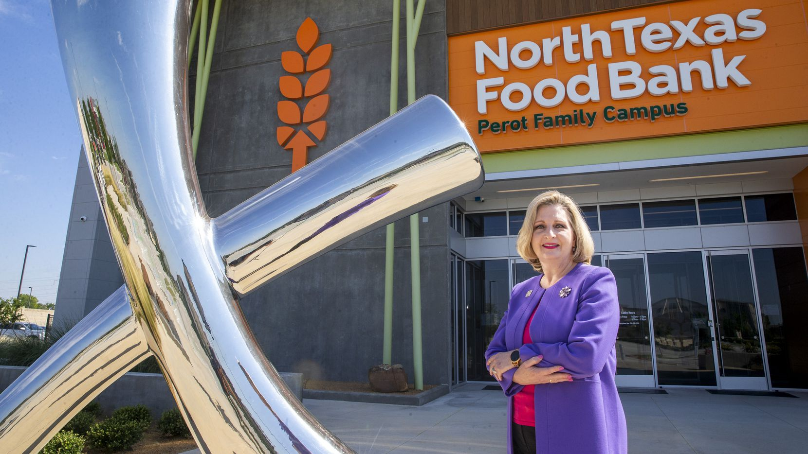 Trisha Cunningham, CEO and president of the North Texas Food Bank, stands next to a sculpture at the North Texas Food Bank Perot Family Campus in Plano. The piece is called Lulu May's Mark and is a tribute to the mother of the late Ross Perot Sr. and his sister, Bette Perot.