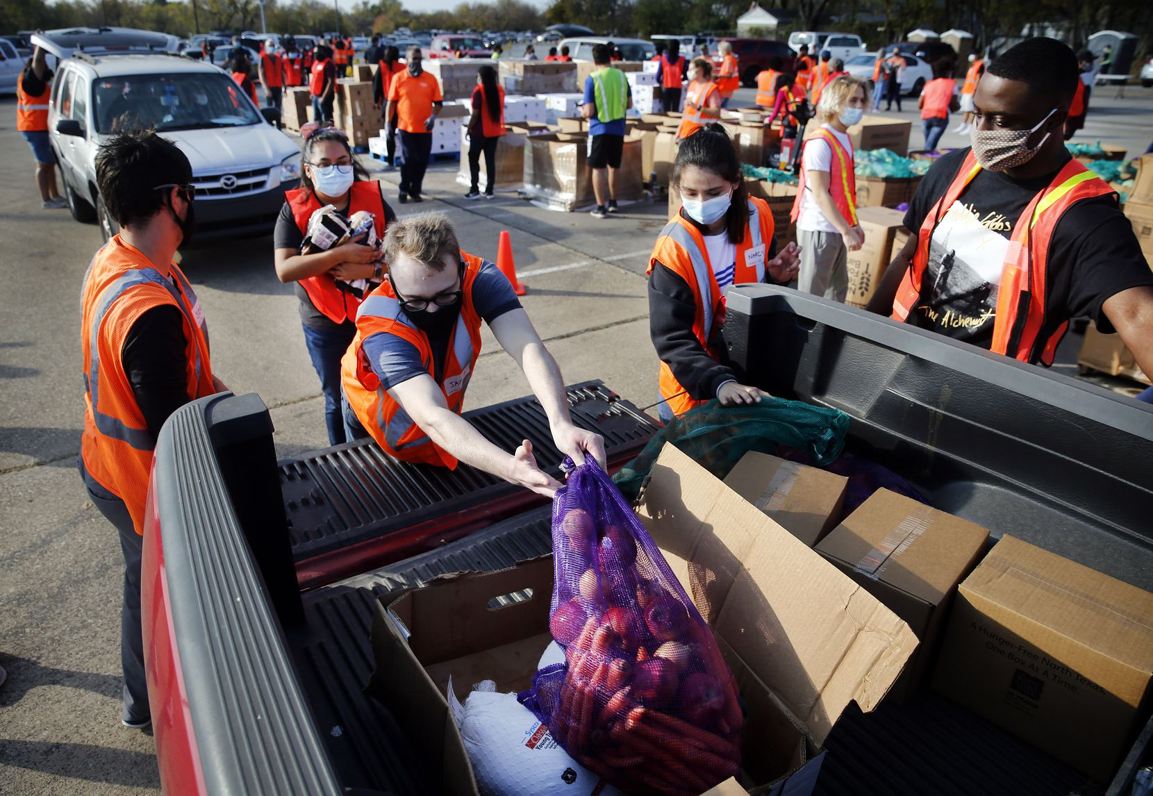 A team of volunteers loaded vehicles with bagged fruits and vegetables, cartons of dry goods and frozen turkeys for distribution to families lined up at Fair Park in Dallas, Saturday, November 14, 2020. (Tom Fox/The Dallas Morning News)